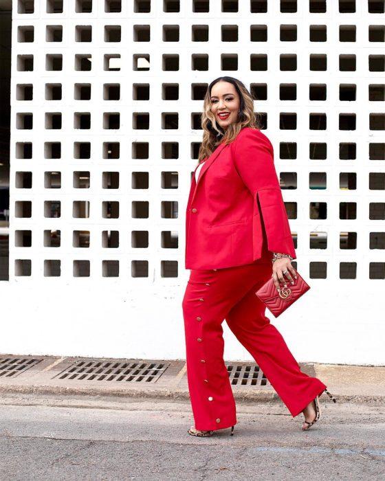 una mujer camina frente a una barda de cuadros, va vestida con traje de pantalón y saco rojos y un bolso de mano rojo