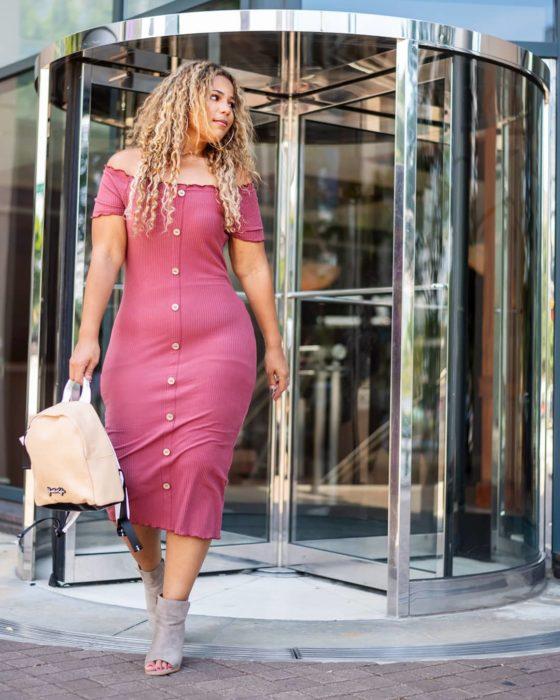 Mujer con vestido rosa saliendo de una puerta giratoria de un centro comercial con una bolsa en la mano