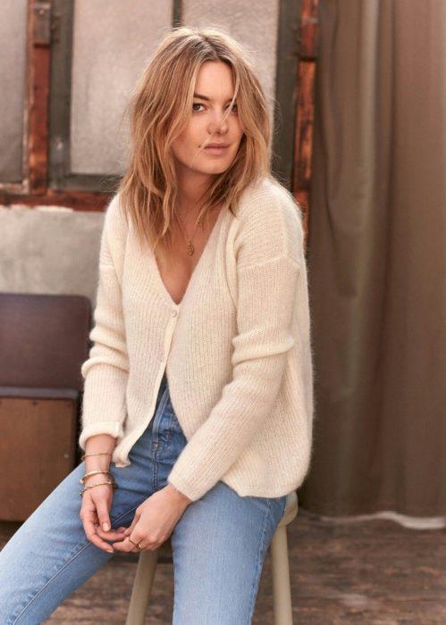 Outfits con cardigans; mujer rubia con suéter blanco de botones y jeans