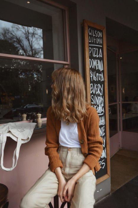 Outfits con cardigans; chica en cafetería con cabello castaño rojizo, suéter anaranjado con botones y pantalón caqui