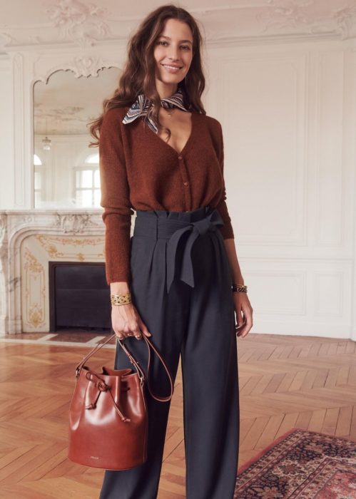 Outfits con cardigans; mujer de cabello castaño largo, con suéter café con escote en v, pañoleta en el cuello y pantalón de vestir con lazo y moño como cinto