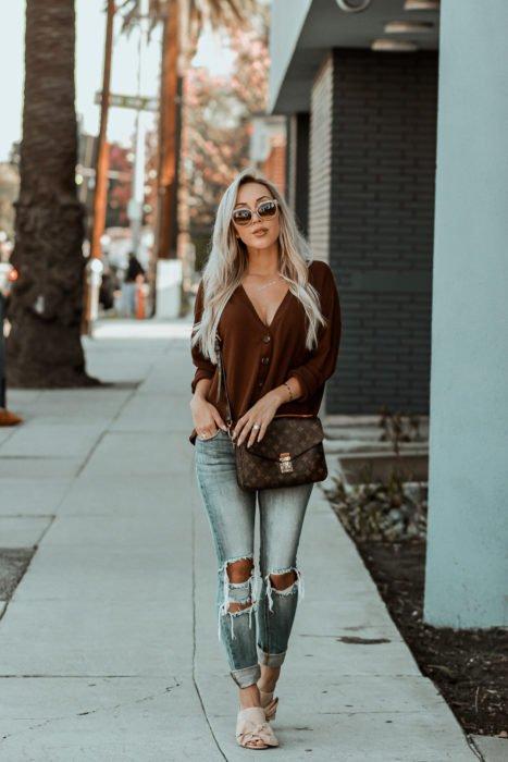 Outfits con cardigans; chica de cabello rubio platinado caminando por la calle, vestida con suéter de botones café y pantalón desgastado de mezclilla