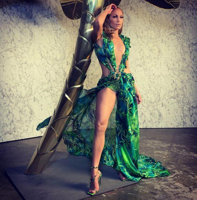 Jennifer Lopez posando para una foto con el vestido verde jungla de Versace