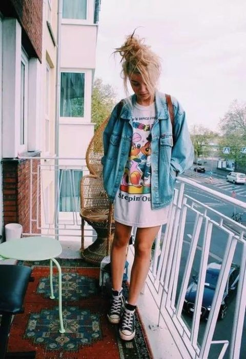Chica en un balcón llevando camisa larga con estampado de dibujos animados