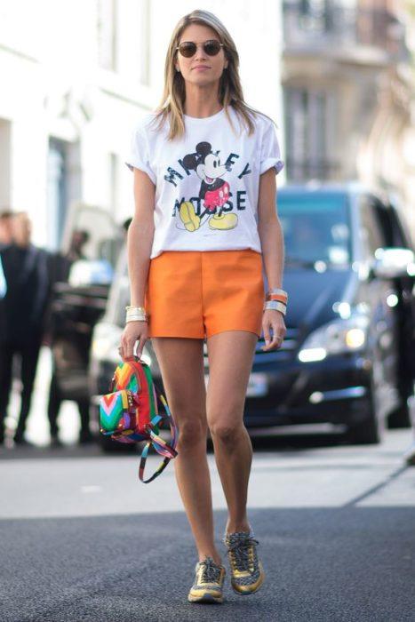 Chica con short naranja y camisa estampada con Mickey Mouse caminando por las calles