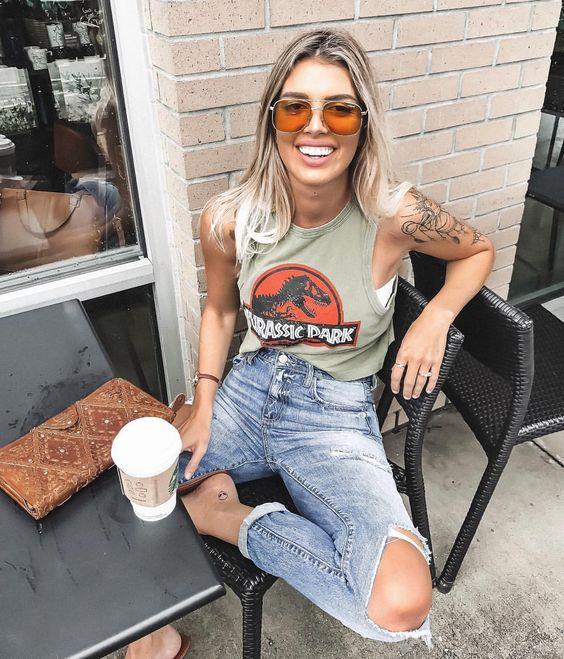 Chica fuera de una cafetería, sentada, sonriendo, llevando outfit con playera de Jurassic Park