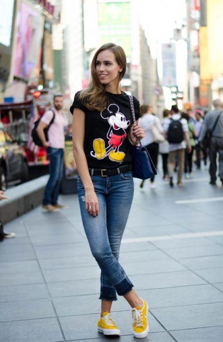 Chica paseando por las calle y modelando un outfit con camisa estampada de Mickey Mouse