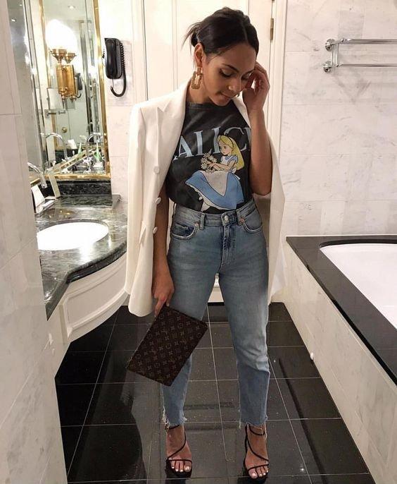 Chica dentro de un baño, llevando outfit con blazer y camisa estampada de Alicia en el país de las maravillas