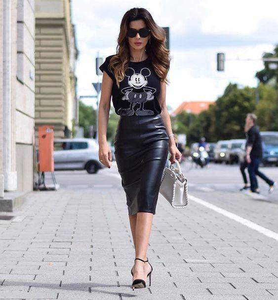 Chica caminando pro la calle llevando outfit con falda lápiz y blusa estampada de Mickey Mouse