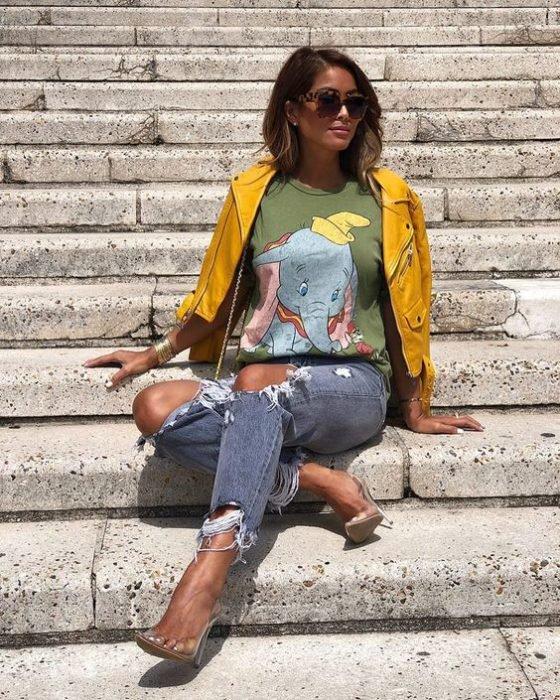 Chica sentada sobre unos escalones, modelando outfit con camisa estampada de Dumbo