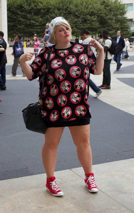 Mujer en una banqueta con una mini falda negra y una playera con Micky Mouse, tenis rojos con cintas blancas