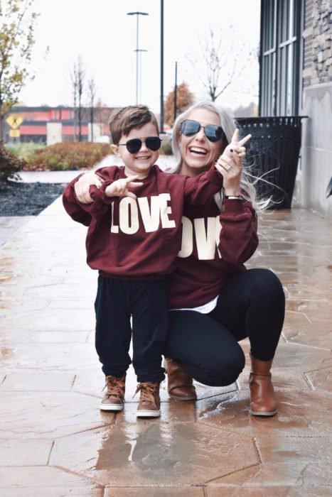 Madre e hijo usando outfit similares con sudadera color vino, pantalón de mezclilla y zapatos color caqui
