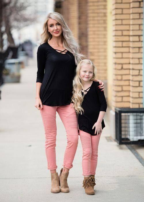 Madre e hija usando outfits iguales con suéteres negros, pantalones rosa palo y zapatos color caqui