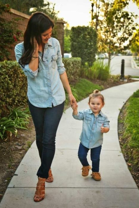 Madre e hija caminando por el parque con jeans en azul marino, camisas ligeras de mezclilla azul cielo