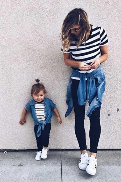 Madre e hija con leggins oscuros, camisa a rayas y chamarra ligera de mezclilla