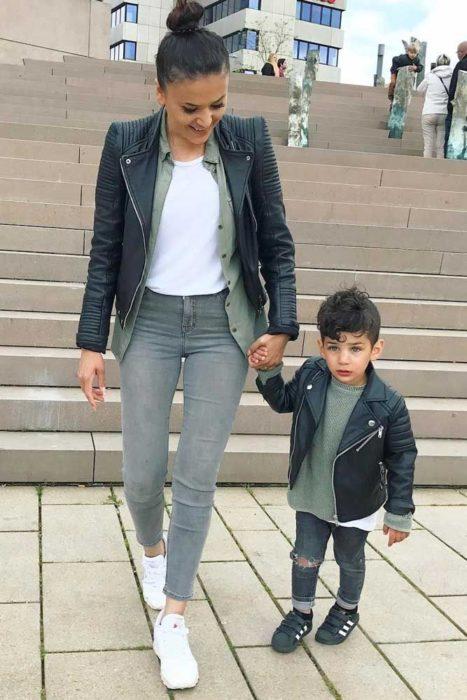 Madre e hijo usando jeans de mezclilla, chaqueta de cuero y camisas lisas