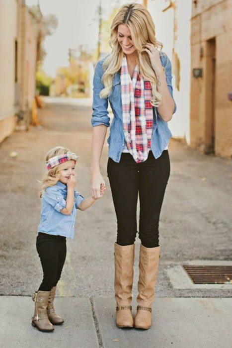 Madre e hija tomadas de la mano, llevando outfits iguales con jeans oscuros, botas altas y camisas a cuadros