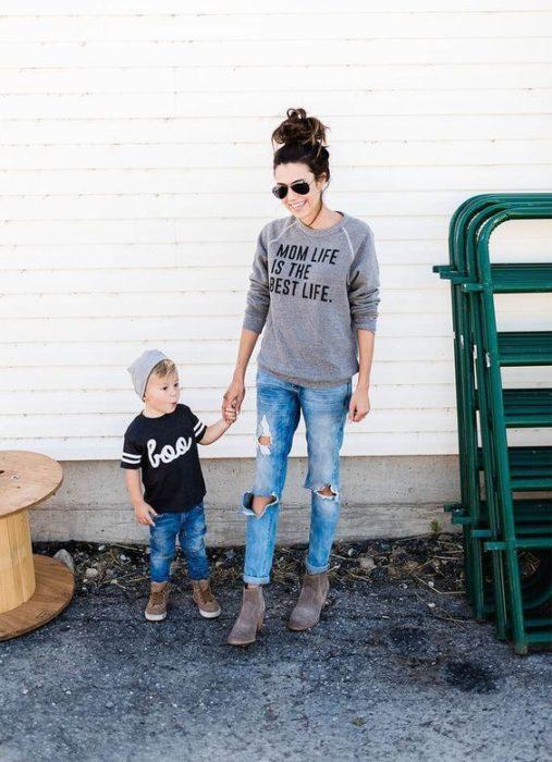Madre e hijo tomados de la mano, compartiendo outfits con jeans rotos, sudaderas ligeras y botas en gris