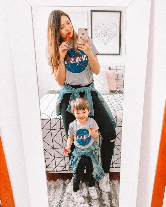 Madre e hijo frente al espejo tomando una selfie, mostrando sus outfits a juego con playeras de la NASA