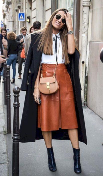 Chica usando falda larga de color ladrillo, blusa blanca, botines y abrigo largo de color negro