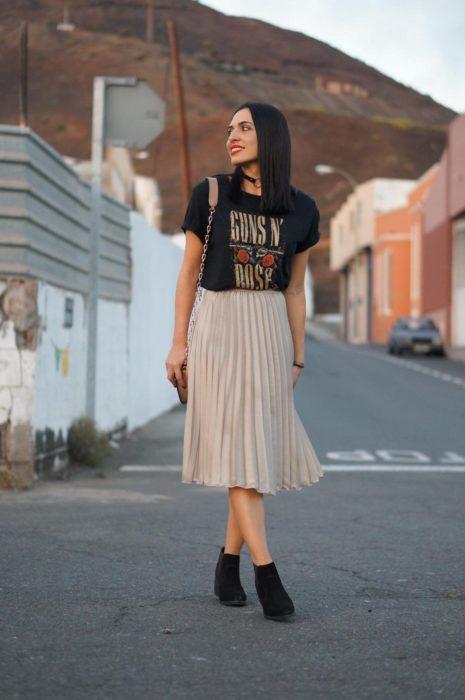 Chica usando una falda de color café, playera estampada y botines de color negro