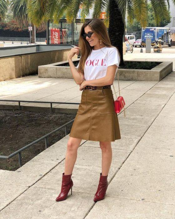 Chica usando una falda de color camel, botines rojos y camisa blanca