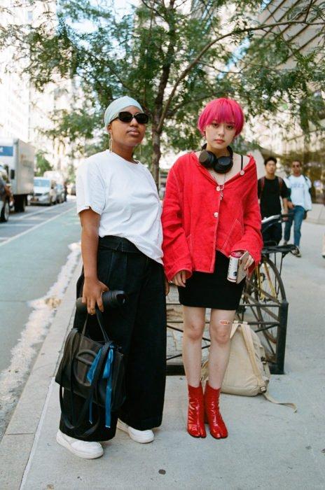 Estudiantes de Parsons y New School muestran sus atuendos para su primer día de clases; amigas, chica morena y chica asiática en la calle con ropa a la moda