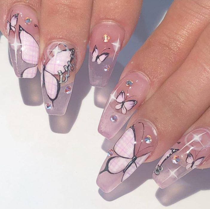 Chica con unas uñas de mariposa en colores nude con rosa
