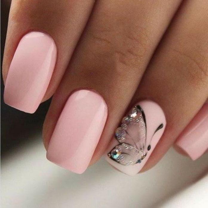 Chica con unas uñas de mariposa en color rosa y brillos de color tornasol