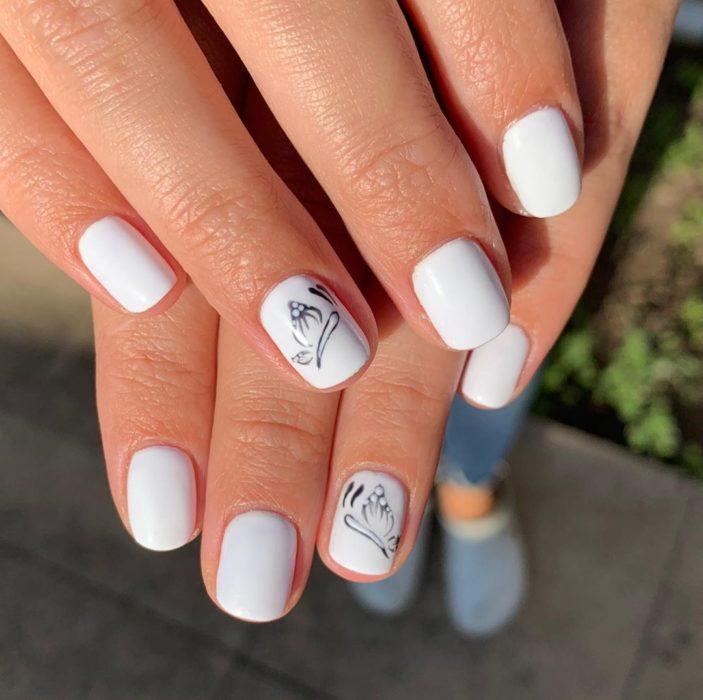 Chica con unas uñas de mariposa en color blanco con negro