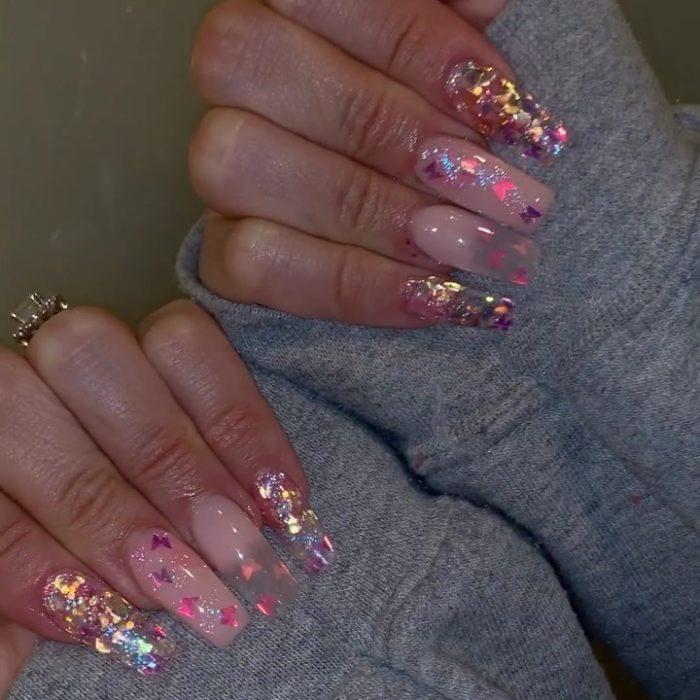 Chica con unas uñas de mariposa en color rosa con mariposas tornasol