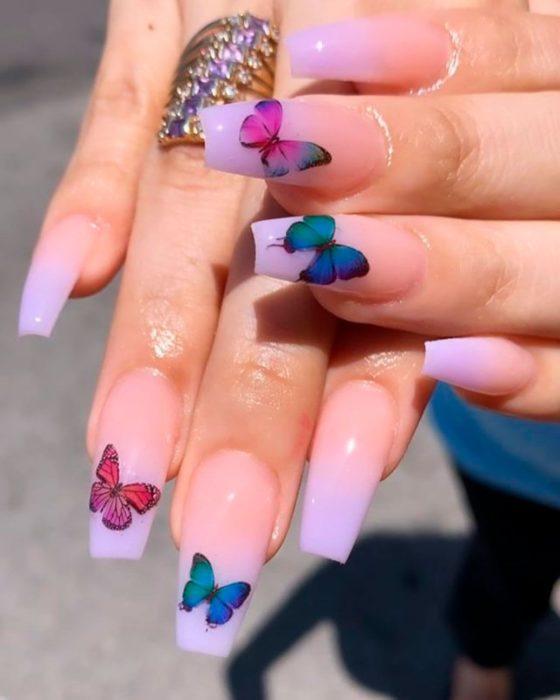 Chica con unas uñas de mariposa en color lila con rosa y verde