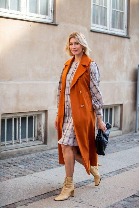Chica caminando mientras usa unos botines witch de color cameo, vestido y suéter naranja