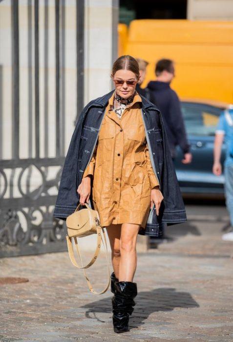 Chica usando unos botines de color negro, vestido color camel y chamarra de mezclilla