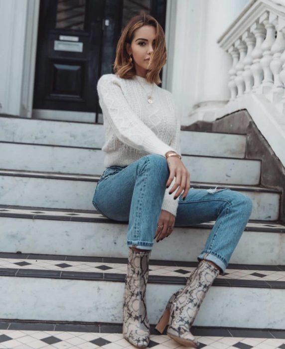 Chica sentada en unas escaleras durante una sesión de fotos mientras usa un sueter blanco, jeans y botas de estampado animal