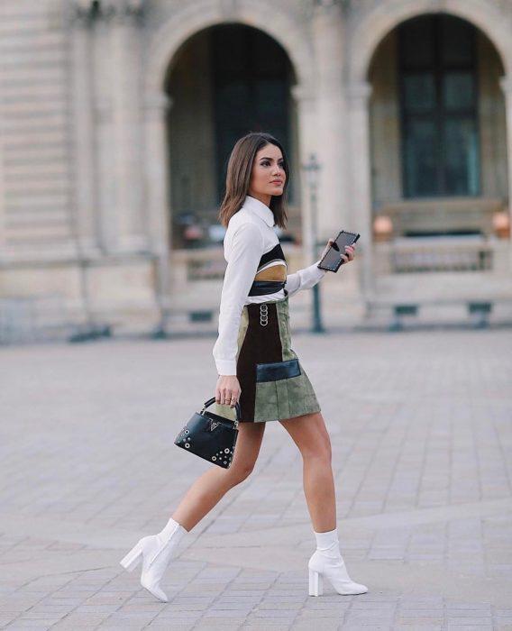 Chica caminando por las calles mientras usan un vestido estampado y botas blancas