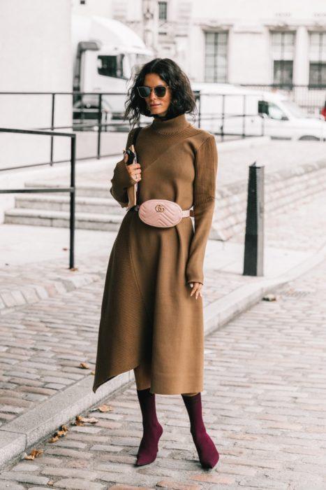 Chica usando un vestido largo color camel con unos botines de color morado