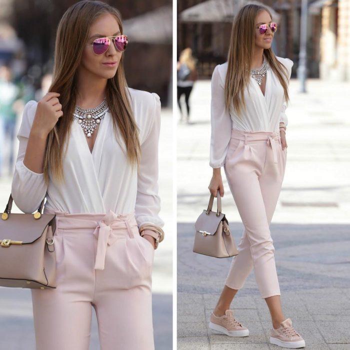 Mujer usando un atuendo rosa claro de vestir con tenis y bolso color rosa