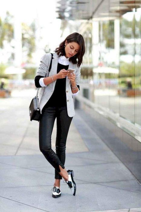 Chica parada mirando el celular mientras usa un conjunto de color negro y saco de color gris
