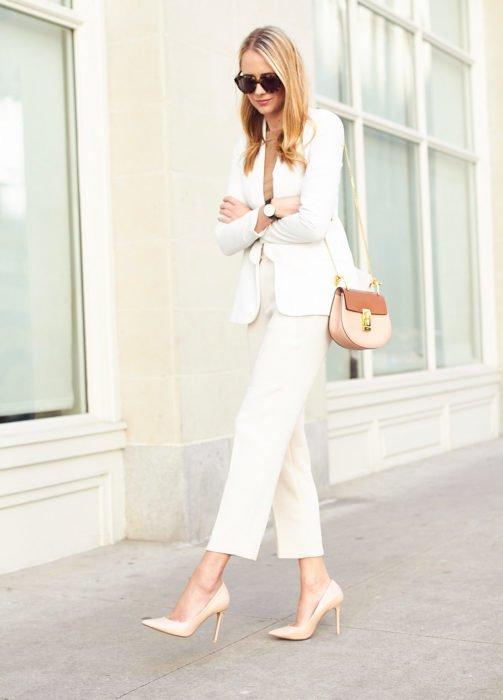 Chica usando un outfit de color blanco con zapatos y bolsa del mismo tono