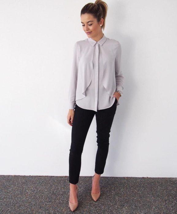 Chica usando una blusa de seda con pantalones pitillo y stilettos