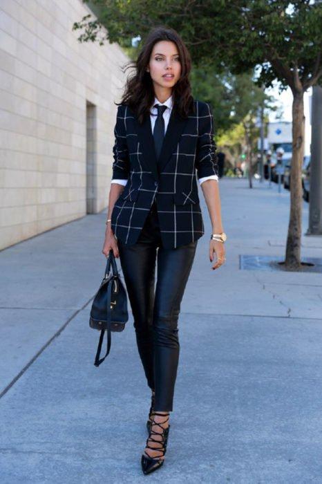 Chica usando un traje con corbata, pantalones de piel y bolso mientras camina por la calle