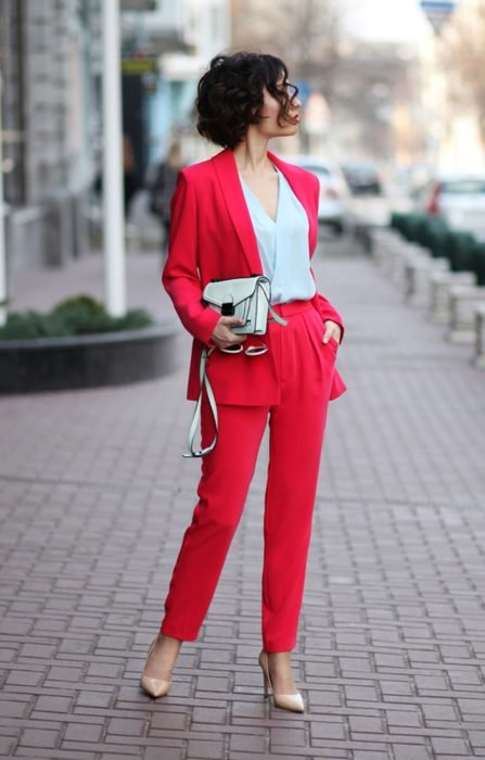 Chica usando un traje rojo, blusa blanca y bolso chico