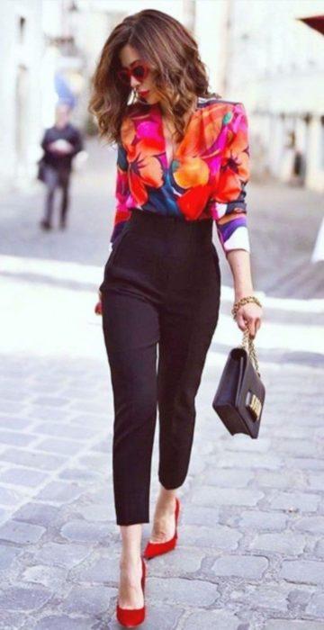 Chica usando una blusa de gasa con estampado floral y pantalones de color negro