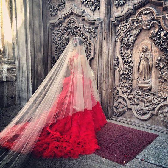 Una novia de vestido rojo y velo blanco a las puertas de un templo