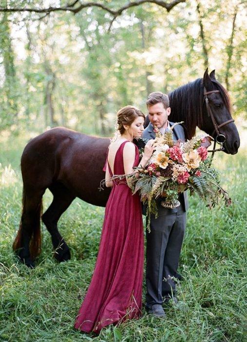 Una pareja de novios posa a un lado de un caballo frisón negro, ella con vestido rojo quemado y el novio sostiene el ramo