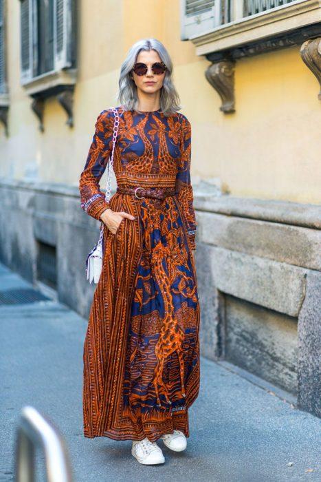 Ropa estilo boho o hippie chic; chica de cabello plateado corto con maxivestido anaranjado y azul con estampado de jirafa, con tenis blancos