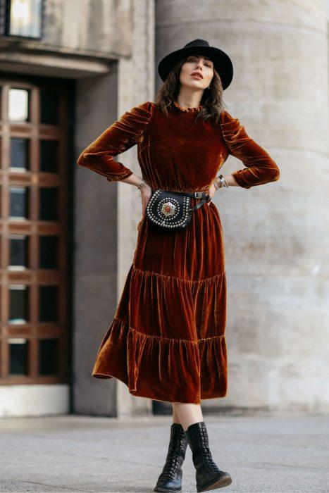 Ropa estilo boho o hippie chic; chica con manos en la cintura, con vestido midi de terciopelo con cangurera, con sombrero y botas militares negras