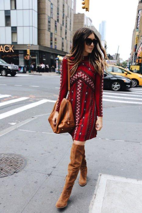 Ropa estilo boho o hippie chic; mujer caminando en la calle con vestido rojo con mangas arriba de la rodilla, botas largas de gamuza y bolsa grande