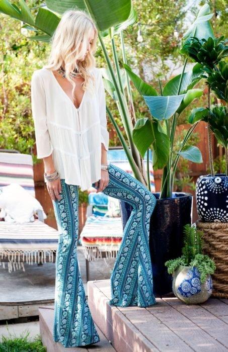 Ropa estilo boho o hippie chic; mujer de cabello rubio platinado y ondulado, con blusa blanca de algodón y pantalón acampanado azul con tela de paliacate